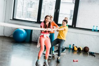 lapsijoukko vetää köyttä liikuntasalissa