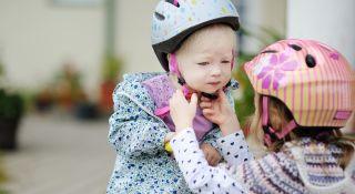tyttö auttaa pikkusiskolle pyöräilykypärän päähän