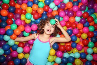 iloinen tyttö makaa värikkäässä pallomeressä pallo otsallaan