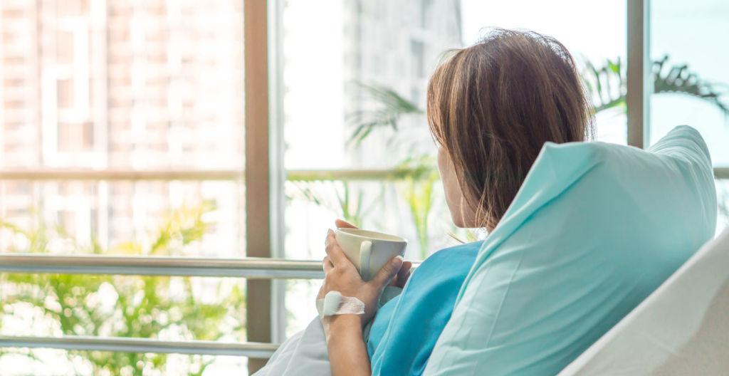 nainen makaa sairaalan sängyssä ja katsoo ulos