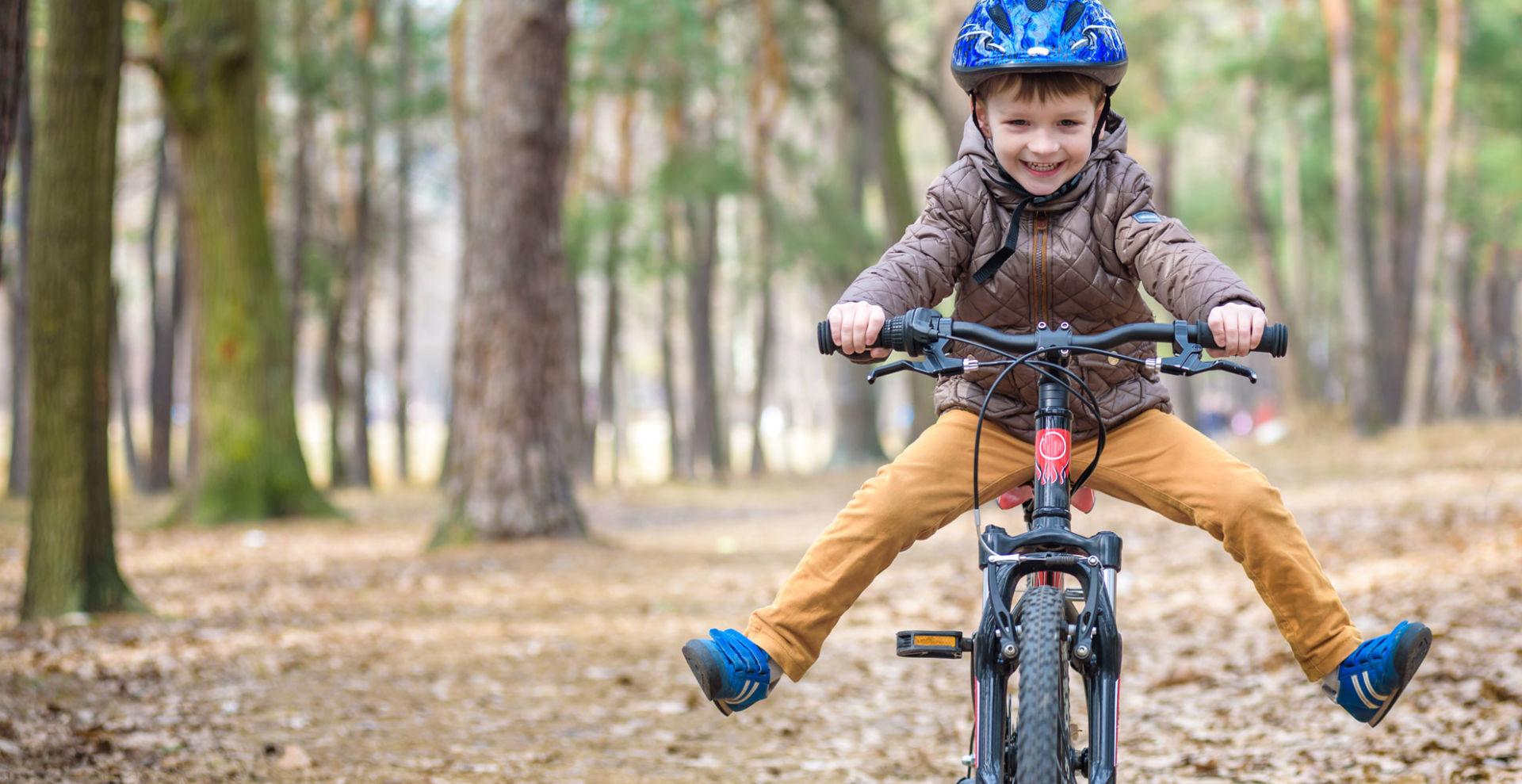 pieni poika ajaa polkupyörällä metsässä