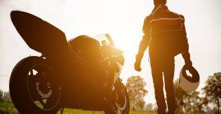 moottoripyörä ja vieressä seisova moottoripyöräilijä auringonlaskussa