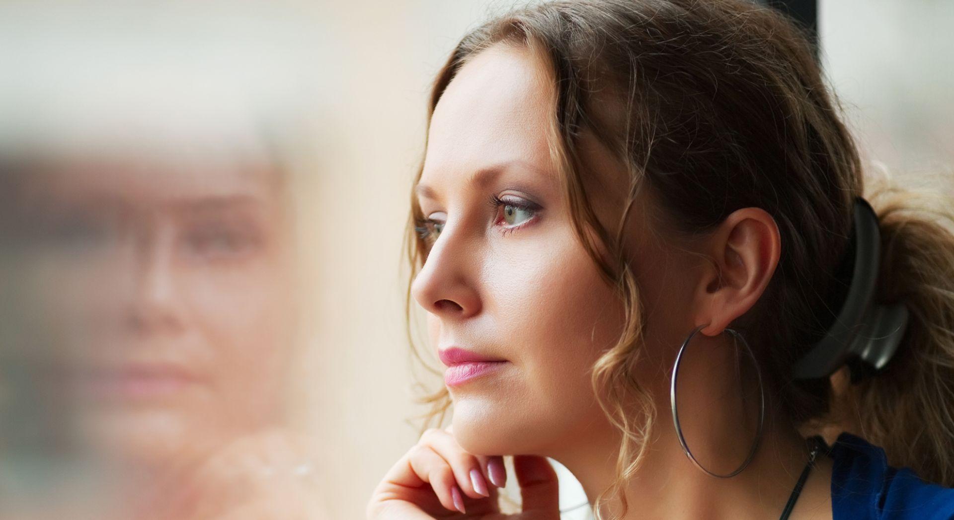 nainen katsoo mietteliäänä ulos ikkunasta
