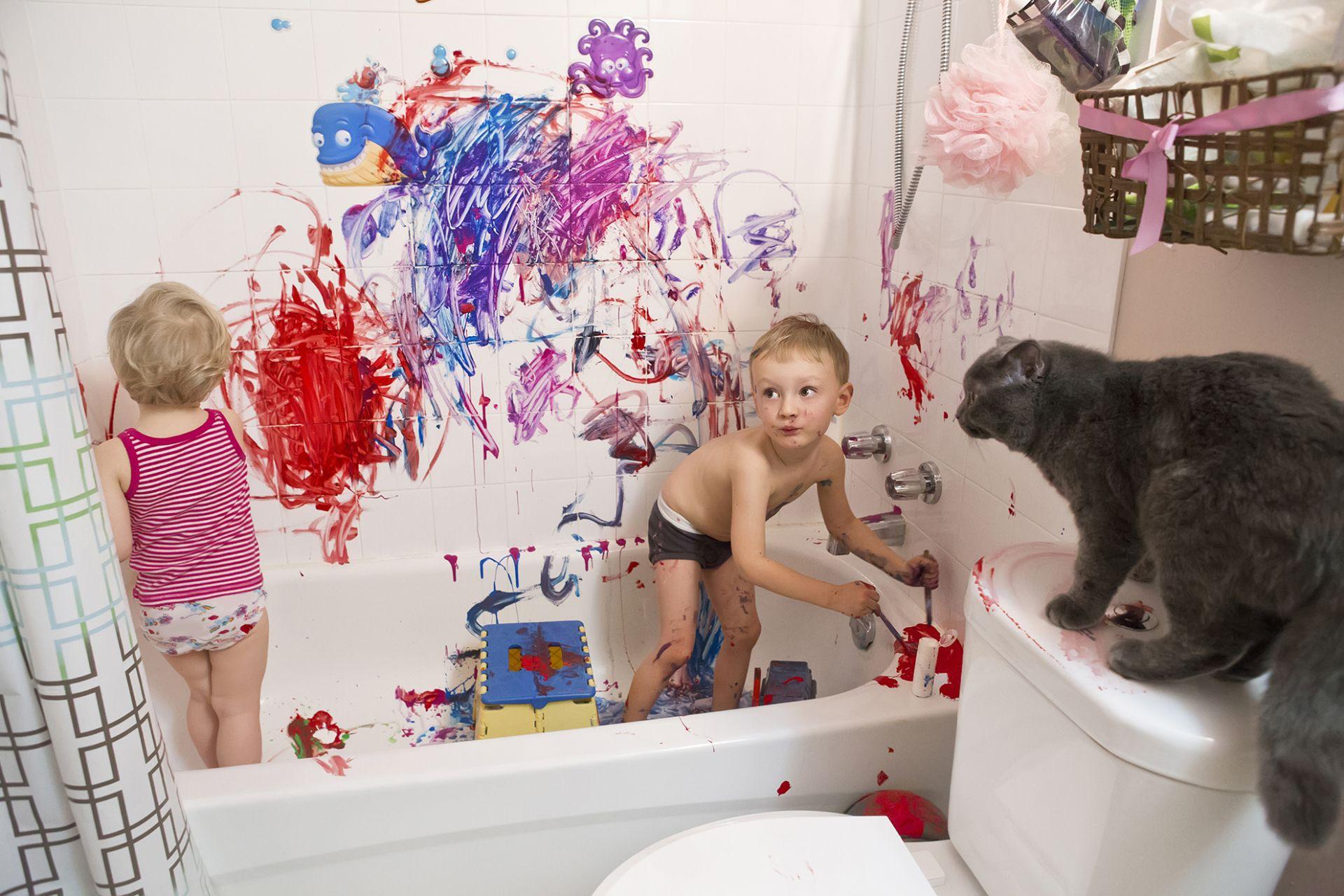 lapset seisovat kylpyammeessa ja ovat maalanneet kylpyhuoneen seinän