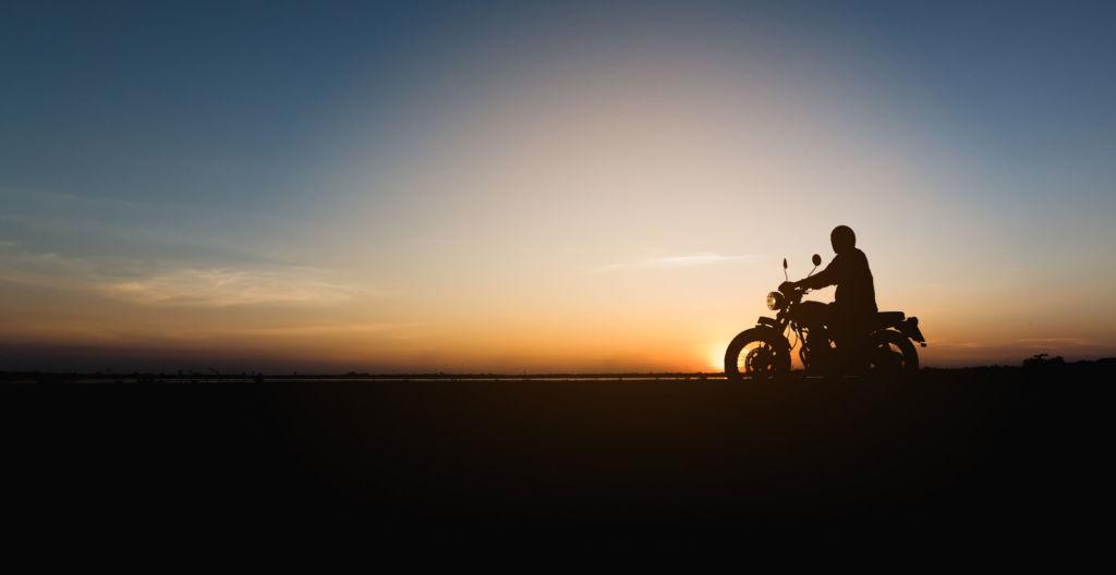 moottoripyörän siluetti illan hämärässä auringonlaskussa