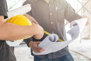 Rakennusmiehet tarkistavat suunnitelmia