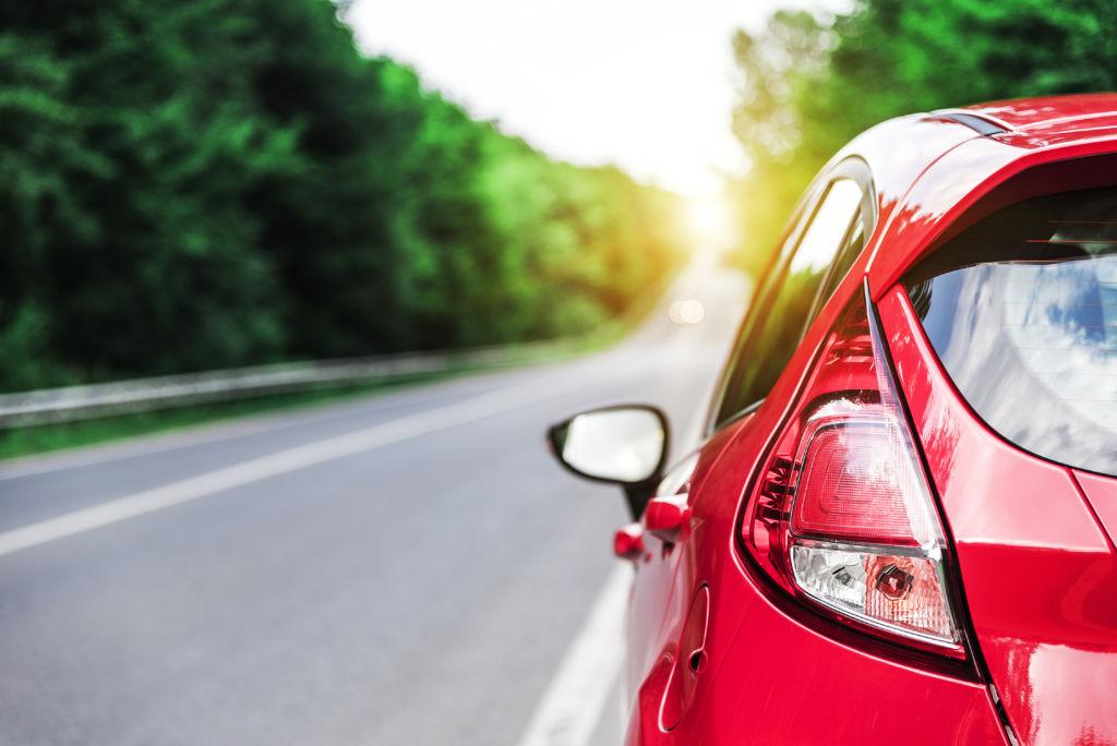punainen auto takaapäin kuvattuna autotiellä