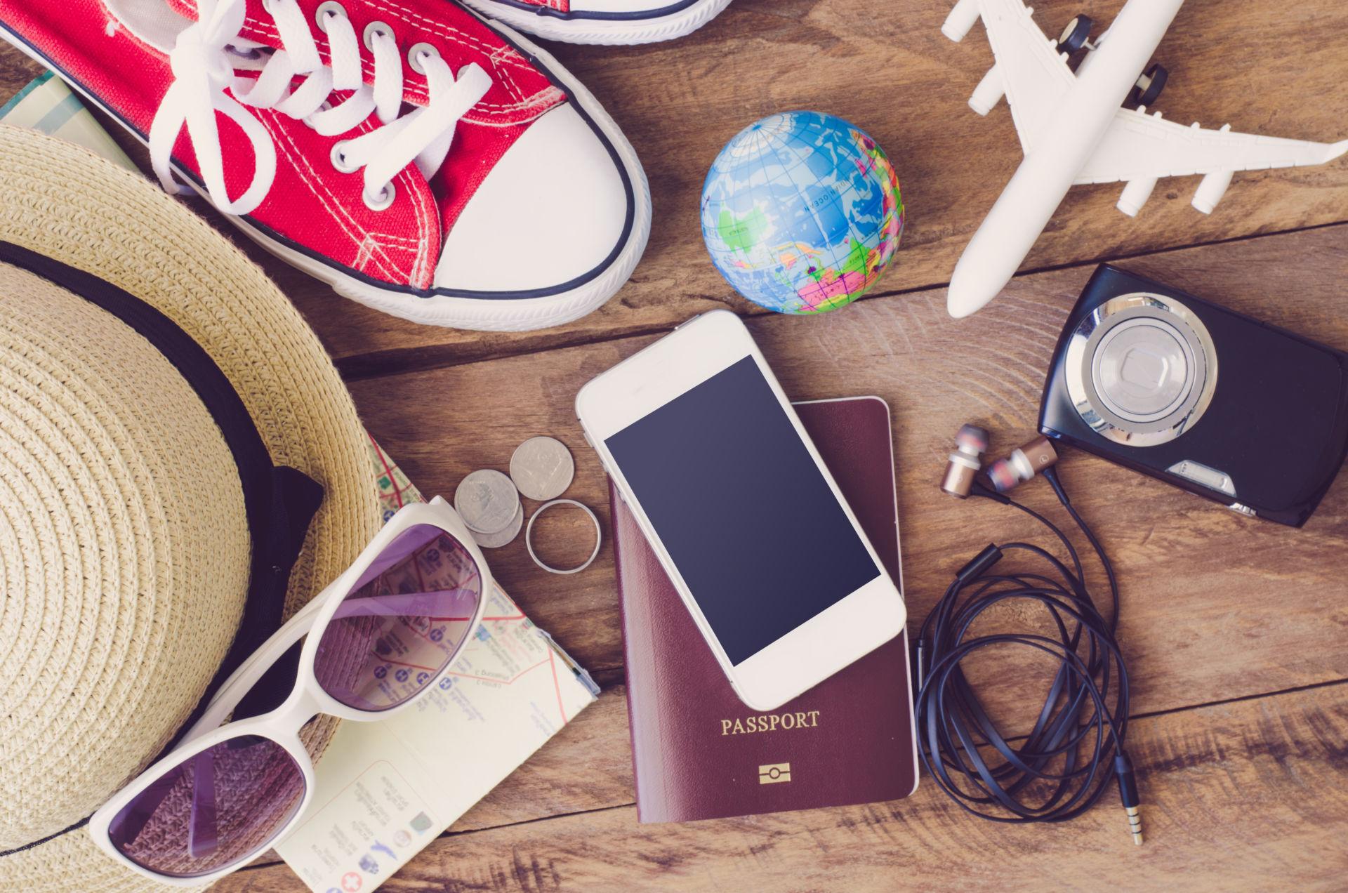Matkalla tarvittavia esineitä, kännykkä, passi, aurinkolasit