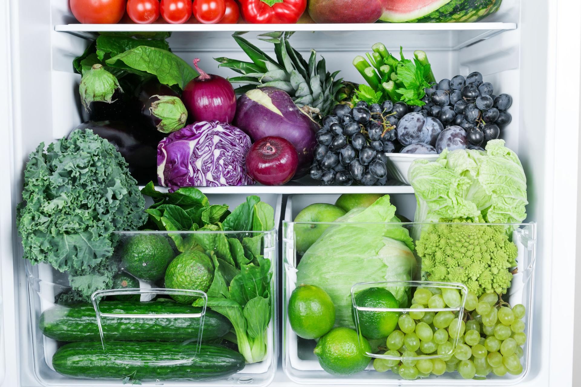 Jääkaappi jossa vihreitä kasviksia ja elintarvikkeita