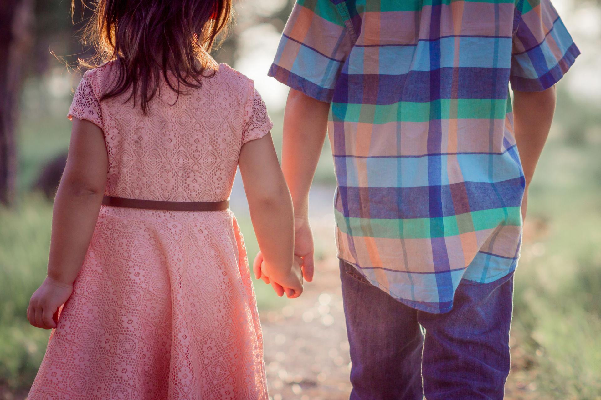 kaksi lasta pitää toisiaan kädestä kiinni