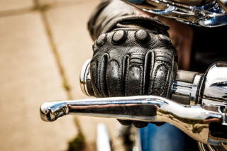 moottoripyöräilijä pitää hanska kädessä kiinni moottoripyörän ohjaustangosta