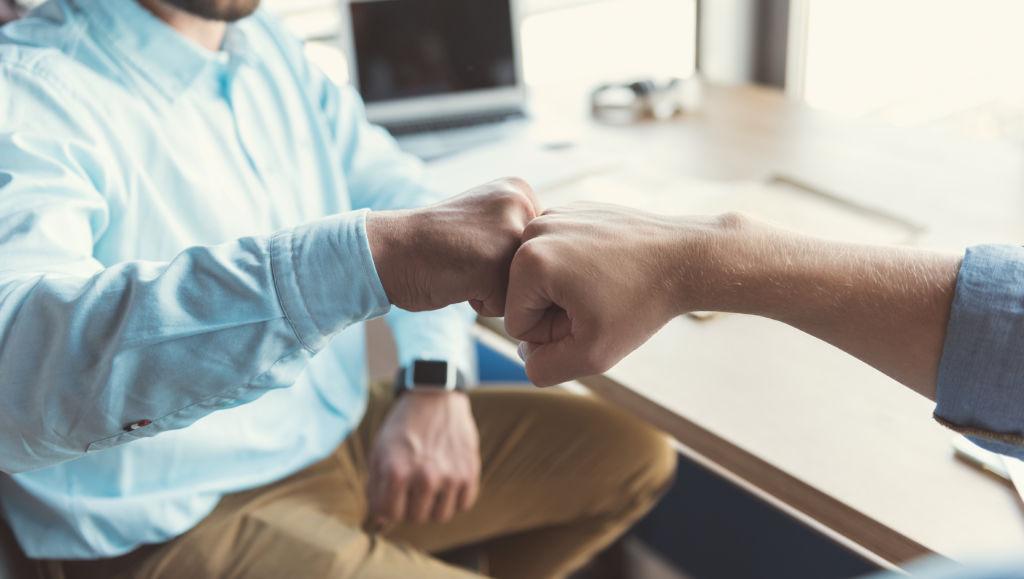 miehet lyövät nyrkit yhteen onnistumisen merkiksi