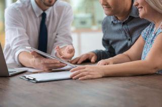 vakuutusasiantuntija keskustelee pariskunnan kanssa pöydän ääressä