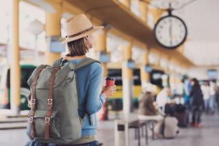 nainen seisoo juna-asemalla katsomassa kelloa
