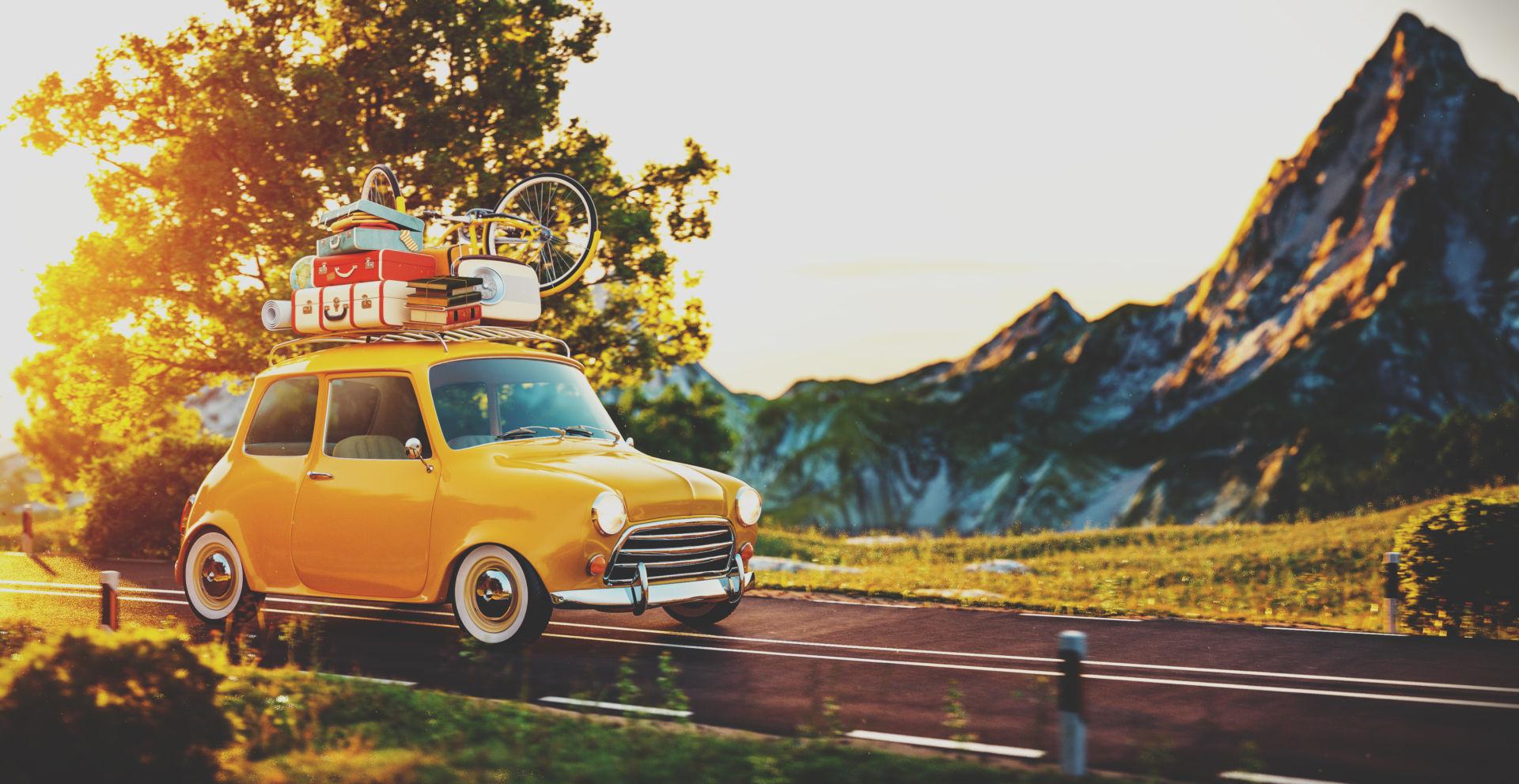 pieni keltainen auto jonka katto on pakattu täyteen tavaraa