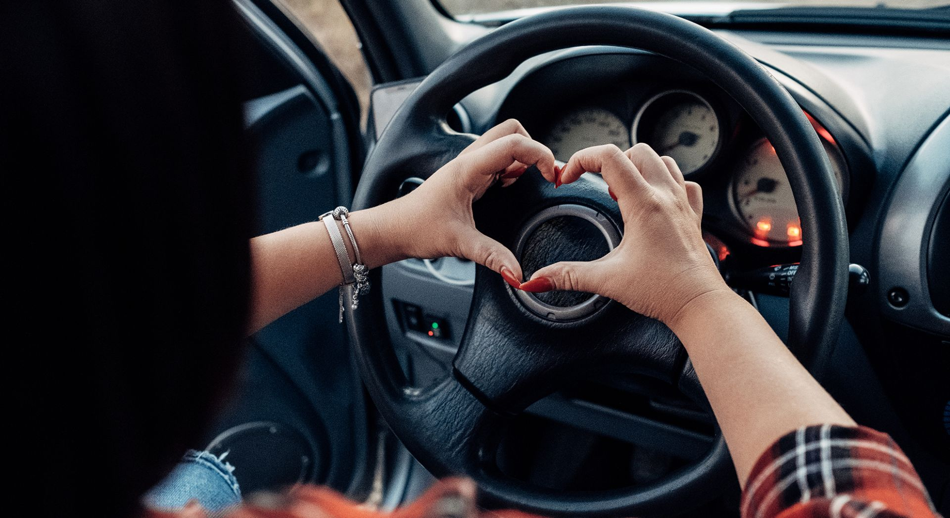 kädet sydämen muodossa auton ratin päällä