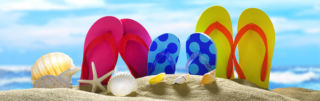 Värikkäät rantatossut pystyssä hiekassa