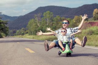 Isä ja poika laskevat lelulla mäkeä