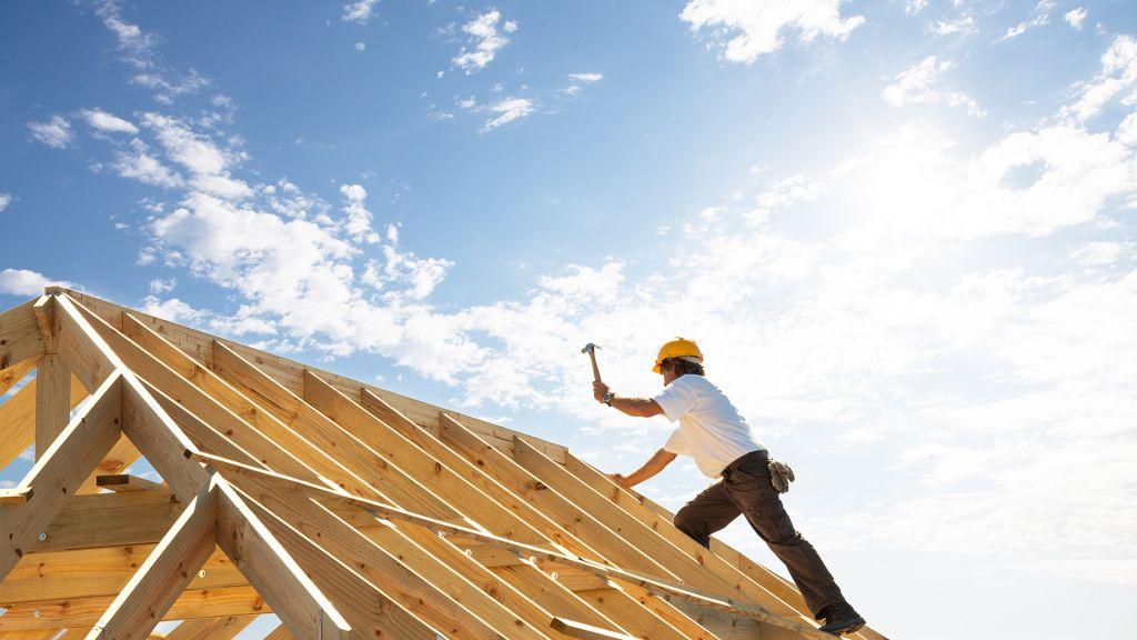 mies rakentaa uuden talon katolla