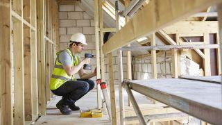 mies poraa puukehikkoa talonrakennustyömaalla