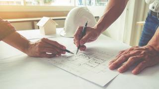 kaksi henkilöä tarkastelee rakennuspiirustuksia