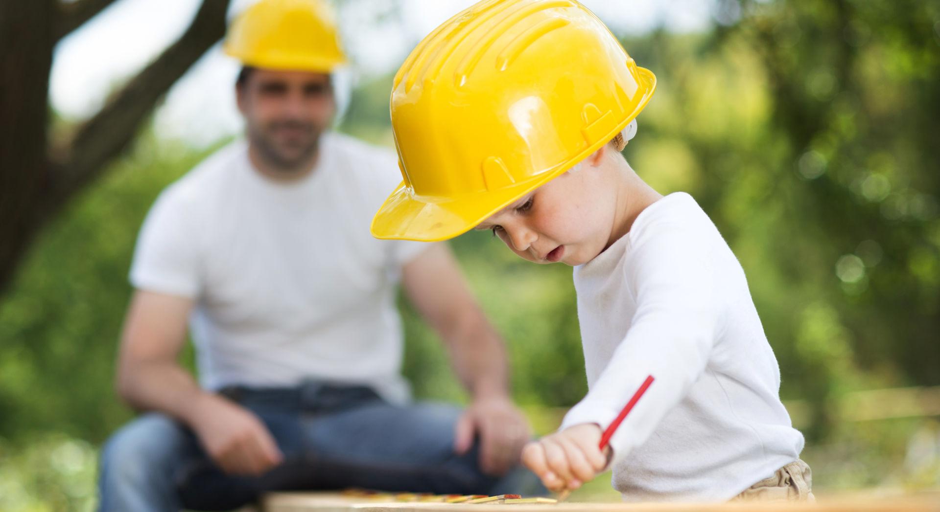 Poika rakentaa isänsä kanssa keltaisessa kypärässään