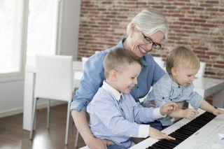 mummo soittaa lasten kanssa pianoa