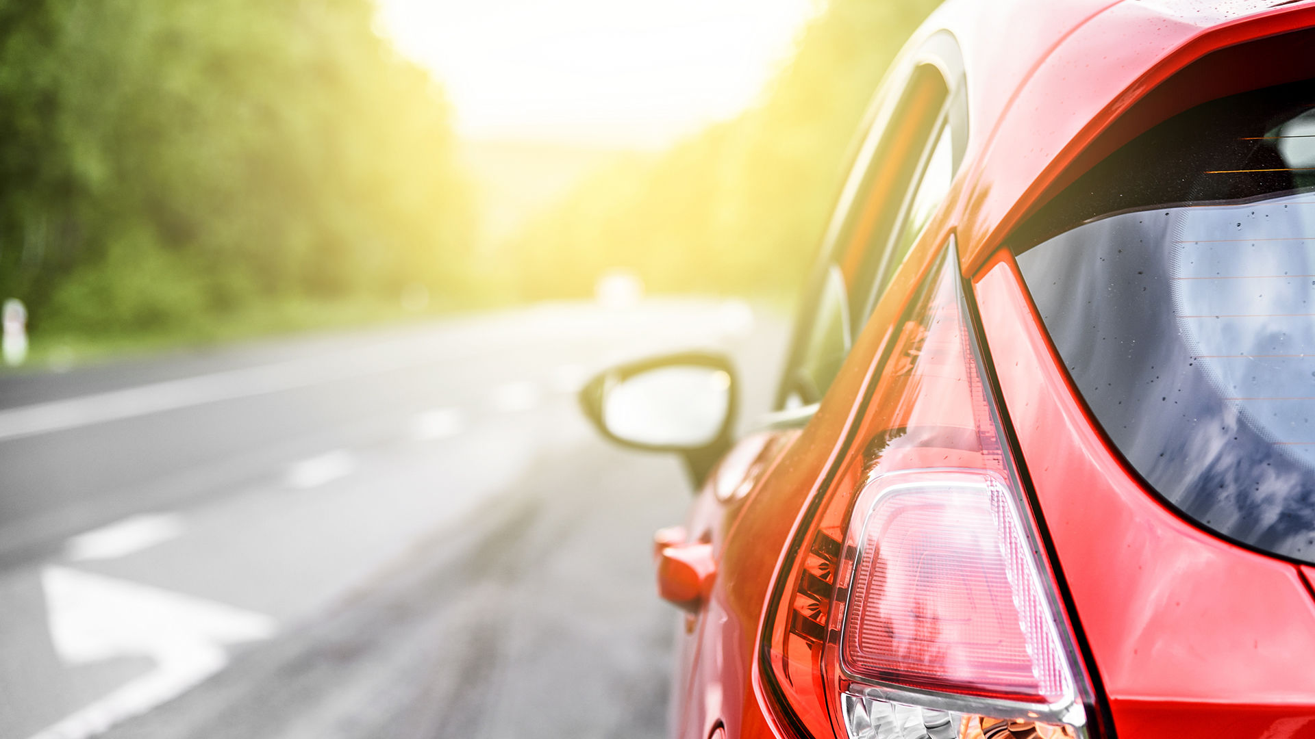 Punainen auto aurinkoa vasten