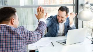 kaksi miestä antaa toisilleen ylävitosen työpöydän ääressä