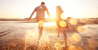 pariskunta juoksee vedessä rannalla auringon laskiessa