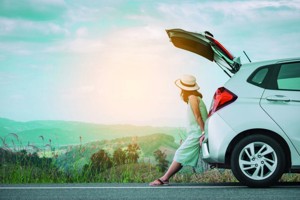 Nainen nojaa valkoisen auton takatilaan ja katselee maisemia