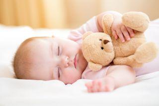 vauva nukkuu pehmolelunallen kanssa