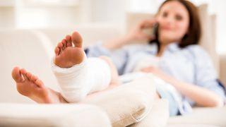 Nainen sohvalla jalka kipsissä