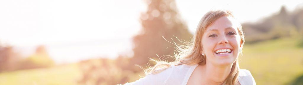 nuori nainen juoksee pellolla auringossa iloisena