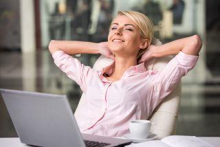 nuori nainen nojaa työtuoliinsa toimistolla läppärin ääressä ja renroutuu