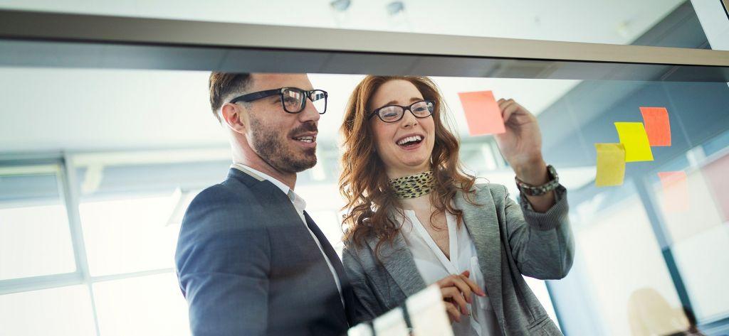mies ja nainen työskentelevät ja ideoivat toimistolla