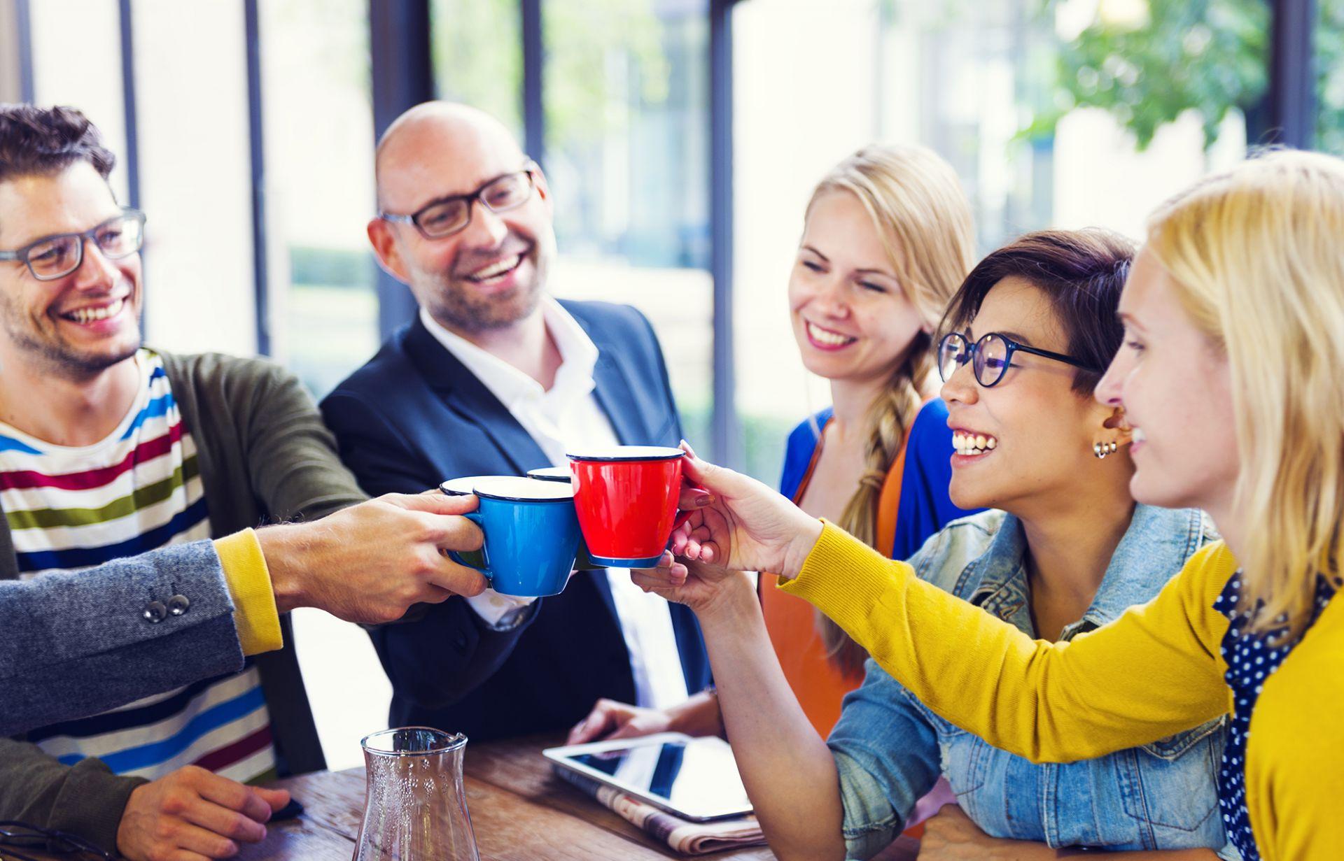 ryhmä iloisia ihmisiä kilistelee kahvikupeilla