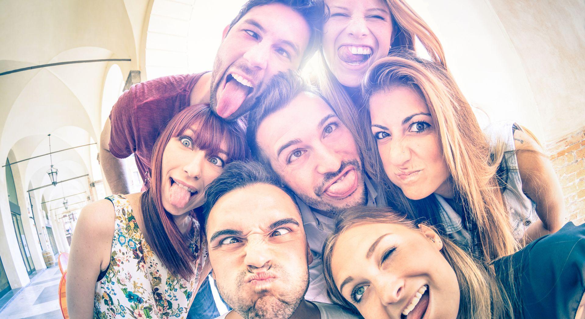 ryhmä nuoria ottaa selfien itsestään ja irvistelee