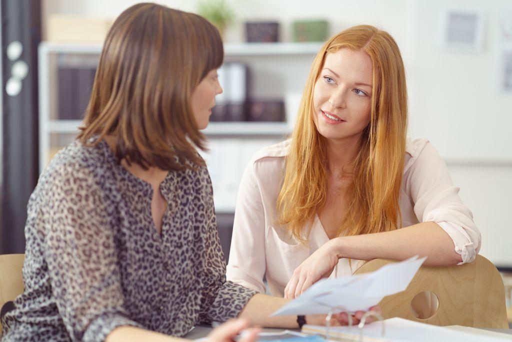 naiset keskustelevat paperit kädessä