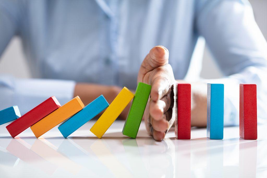 mies estää värikkäiden dominopalikoiden kaatumisen
