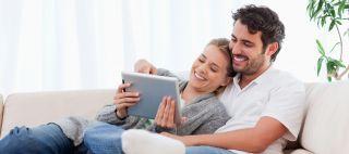nainen ja mies katsovat tablettitietokonetta sohvalla