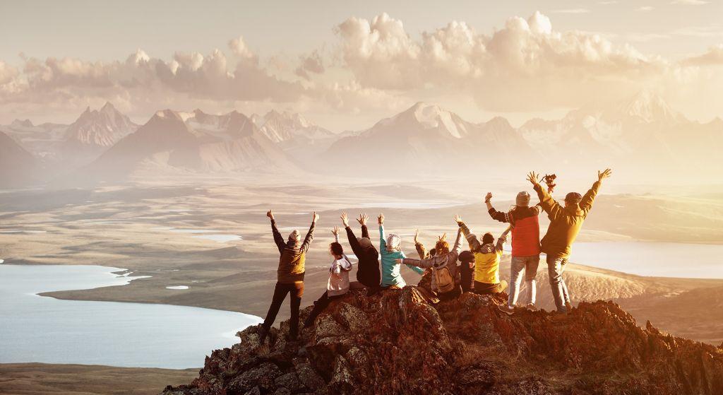 iso joukko ihmisiä seisoo korkean vuoren huipulla
