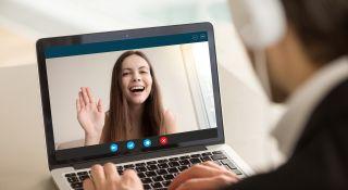nainen vilkuttaa tietokoneen näytöltä verkkoneuvottelussa