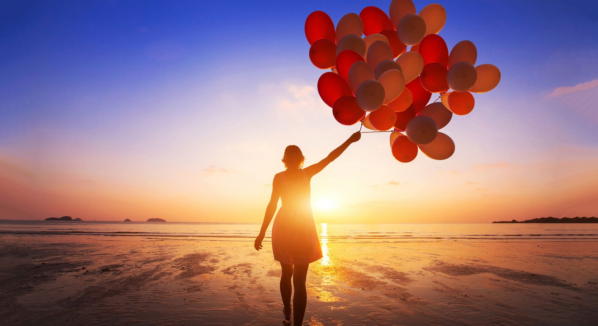 nainen kävelee auringonlaskua kohti iso ilmapallokimppu kädessä