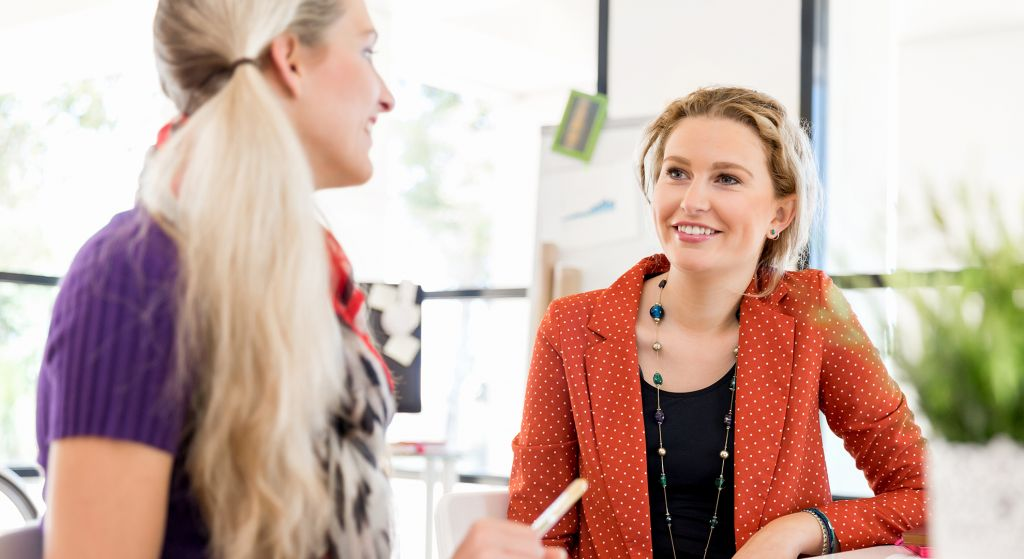 naiset keskustelevat työympäristössä pöydän ääressä