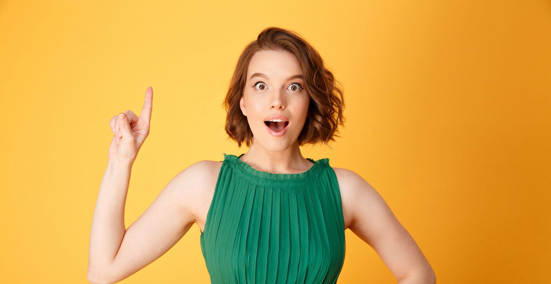 nainen vihreässä mekossa seisoo sormi pystyssä koska on saanut idean