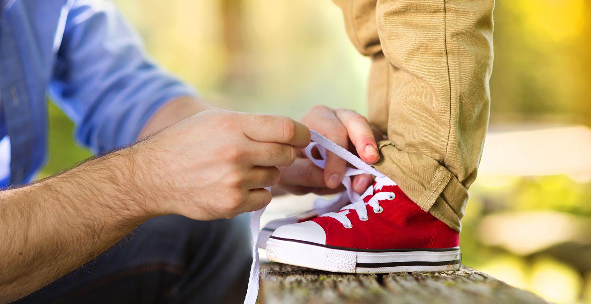 isä sitoo lapsen kengännauhoja
