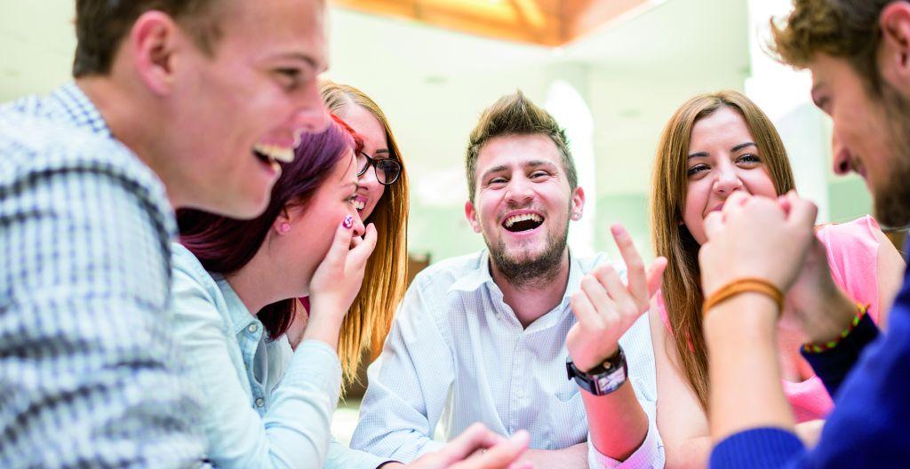 joukko nuoria aikuisia istuu pöydän ääressä nauramassa