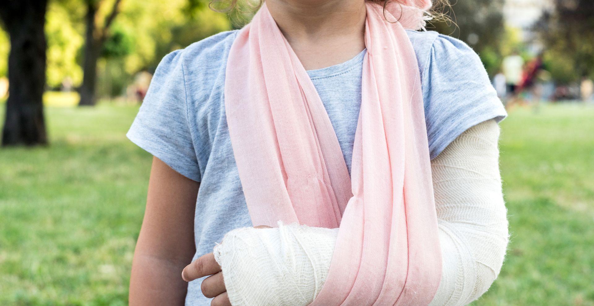 lapsella on vaaleanpunainen kantoside ja kipsi kädessä