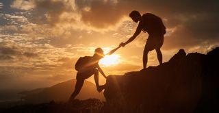 vuorikiipeilijät auttavat toisiaan nousemaan ylös auringonlaskussa